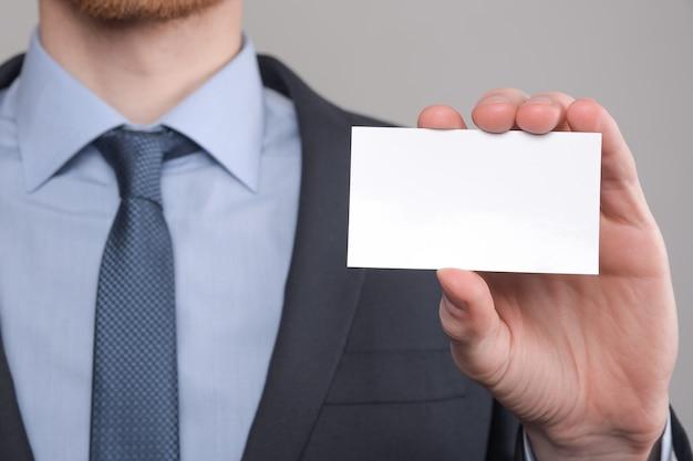 Zakenman, business man's hand houden visitekaartje tonen - close-up shot op grijze tafel. laat een blanco vel papier zien. papieren visitekaartje.