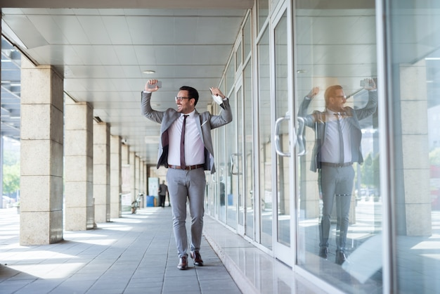 Zakenman celebtating succes in baan. in de ene hand een tablet en in een andere smartphone.