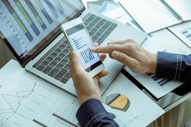 Zakenman controleert de gegevensgrafiek van zijn bedrijf via mobiele telefoons en notebookcomputers.