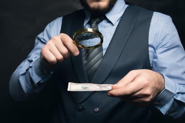 Zakenman controleert geld op vervalsing met een vergrootglas op een zwarte ondergrond