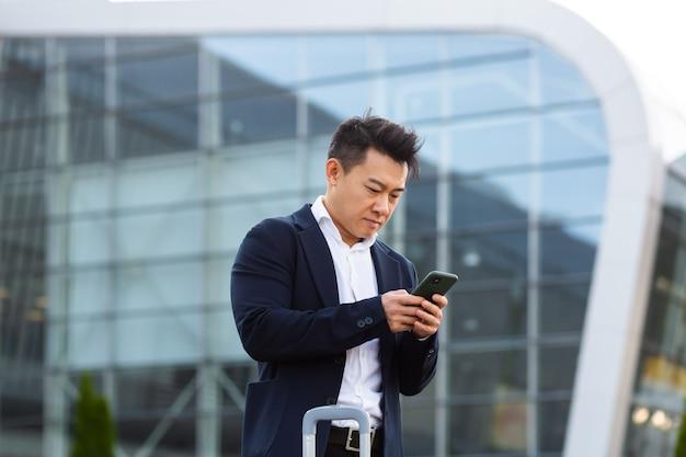Zakenman correspondeerde in een mobiele telefoon gebruikt de messenger-applicatie om op afstand met collega's te communiceren