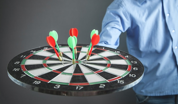 Zakenman dartbord met pijlen houden. doel, bedrijf, succes