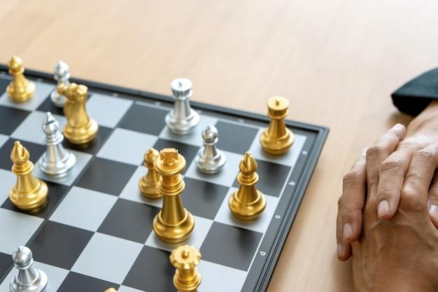 Zakenman denken en houden koning schaken op zijn hand,