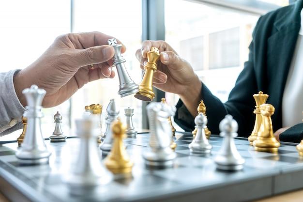 Zakenman denken en koning schaken op zijn hand houden,