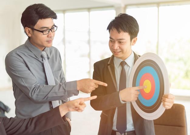 Zakenman die aan bedrijfdoel en jaarlijks doel in vergadering richten die als achtergrond gebruiken (concept groepswerk en vennootschap