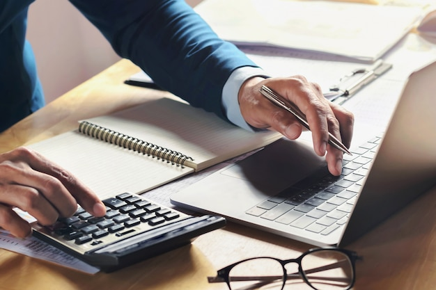 Zakenman die aan bureau met het gebruiken van calculator en computer in bureau werkt. concept boekhoudkundige financiën