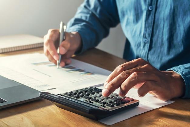 Zakenman die aan bureaubureau werken met het gebruiken van een calculator om begroting, financiën te berekenen