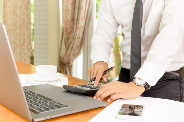 Zakenman die aan calculator werken om financieel plan te berekenen