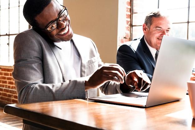 Zakenman die aan de telefoon praat tijdens het gebruik van een laptop