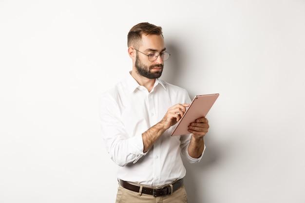 Zakenman die aan digitale tablet werkt, er druk uitziet, over een witte achtergrond staat