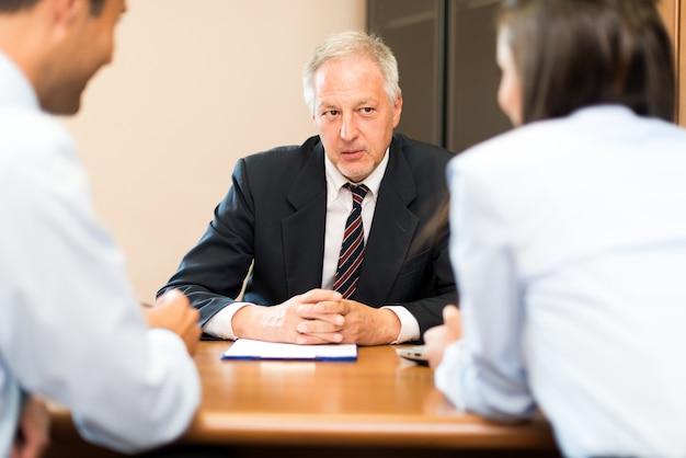 Zakenman die aan een paar in een bureau spreekt