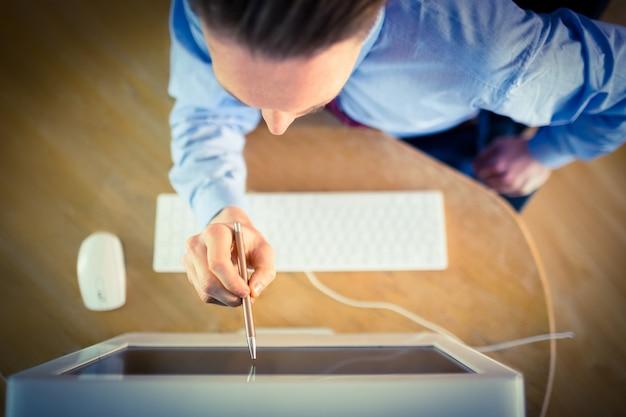 Zakenman die aan het scherm met pen richt