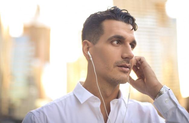 Zakenman die aan iets met oortelefoons luistert