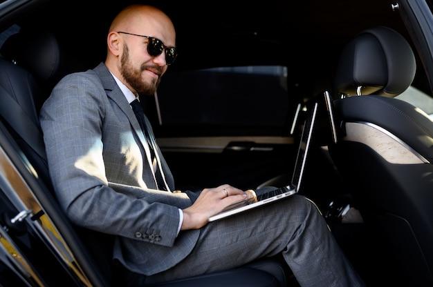 Zakenman die aan laptop in achterbank van uitvoerende auto werkt. concept van zaken, succes, reizen, luxe.