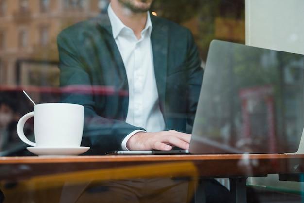 Zakenman die aan laptop in koffie werkt die door glas wordt gezien