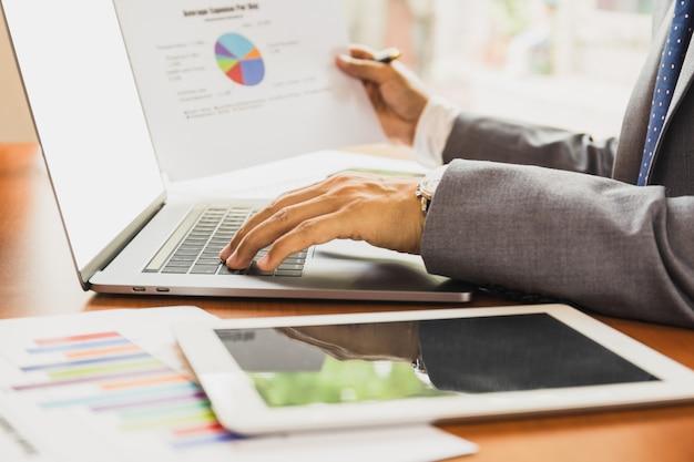 Zakenman die aan laptop werkt en document grafiek financieel diagram houdt.