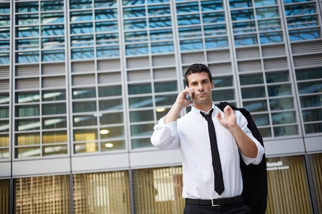 Zakenman die aan mobiel in stedelijk milieu spreekt