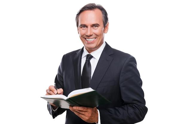 Zakenman die aantekeningen maakt. vrolijke volwassen man in formalwear met notitieblok en glimlachend terwijl hij tegen een witte achtergrond staat
