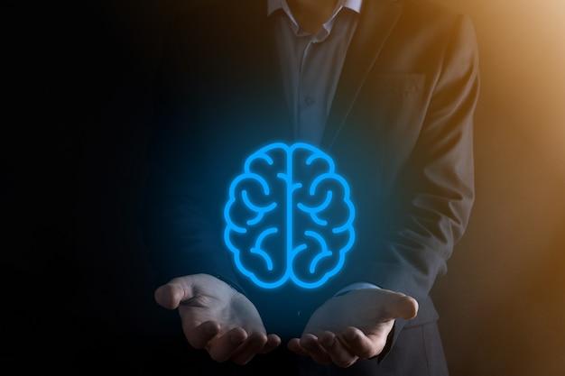 Zakenman die abstracte hersenen en pictogramhulpmiddelen houdt