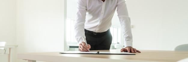 Zakenman die achter zijn bureau staat en naar binnen leunt om een contract of document te ondertekenen.