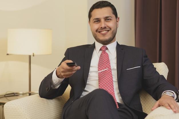Zakenman die afstandsbediening met behulp van terwijl het letten van op tv bij zijn hotelruimte