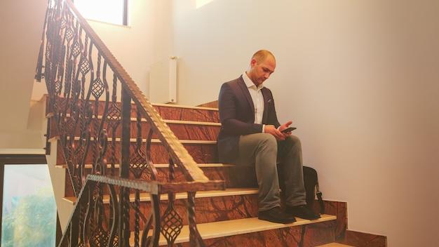 Zakenman die alleen op de trap zit en op smartphone typt in een financiële onderneming die overuren maakt. groep professionele succesvolle zakenmensen die in een modern financieel gebouw werken.