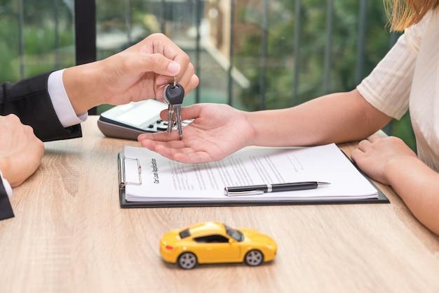 Zakenman die autosleutel over het document van de autoleningstoepassing geeft