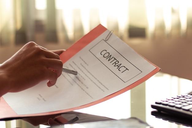 Zakenman die belangrijke documenten lezen alvorens documenten in bureau te ondertekenen.