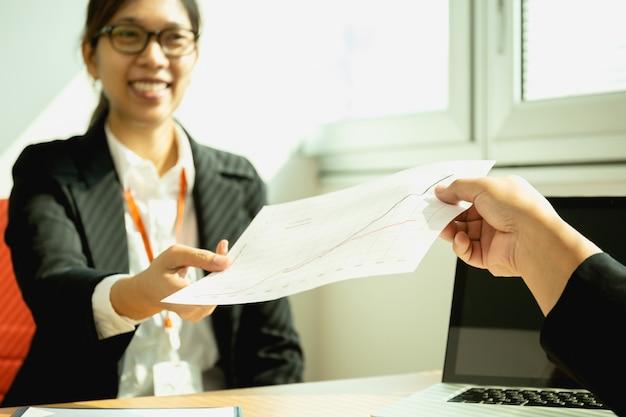 Zakenman die bij bureau met laptop werken die document grafiek overhandigen aan secretaresse.
