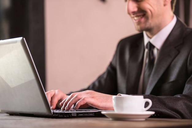 Zakenman die bij laptop met kop van koffie werkt.