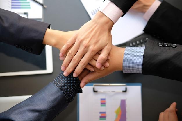 Zakenman die bij verenigde hand, commercieel team wat betreft handen samen aansluiten zich.