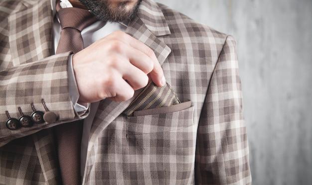 Zakenman die bruine das en jas draagt die zich in bureau bevinden