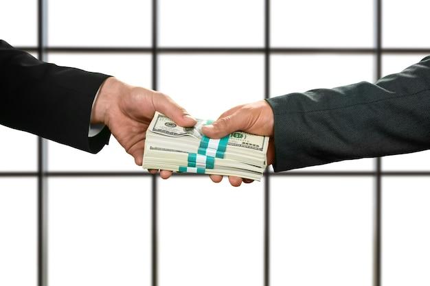 Zakenman die bundels contant geld neemt. groot geld op witte achtergrond. meer dan dankbaar. werkzaam bij verzekeringsmaatschappij.