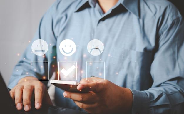 Zakenman die classificatie geeft met gelukkig pictogram, het concept van klantervaringen. positieve beoordeling en feedback, zakenman in pak presenteren uitstekende beoordeling met lachend pictogram voor een tevredenheid.