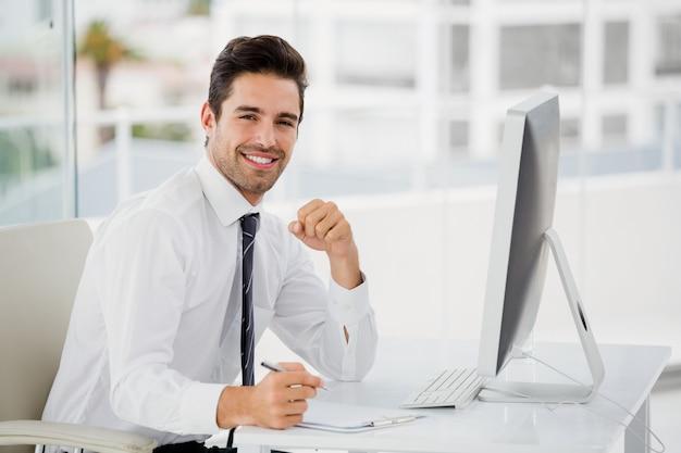Zakenman die computer gebruikt en nota's neemt