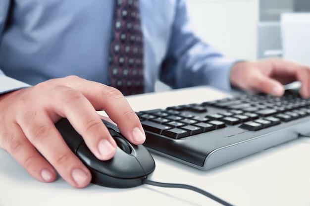 Zakenman die computer met handen met behulp van die op een toetsenbord typen