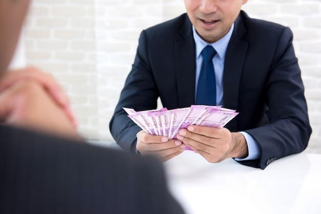 Zakenman die contant geldbeloning in vorm van indisch roepiebankbiljetgeld ontvangen
