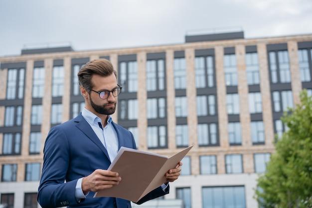 Zakenman die contract leest die documenten analyseert jonge manager die financieel rapport houdt
