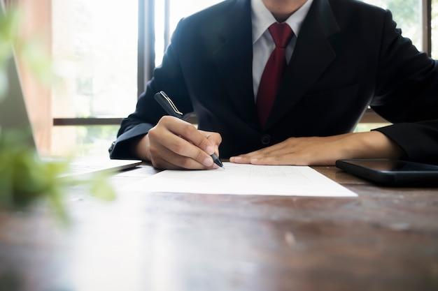 Zakenman die contract ondertekent dat een overeenkomst maakt.