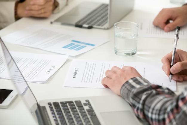 Zakenman die contractvorm van het bedrijfscontract de vullende document ondertekenen op vergadering, close-up