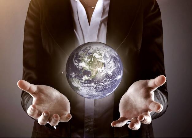 Zakenman die de globe.photo op een grijze achtergrond houdt.