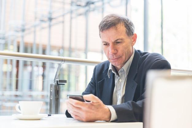 Zakenman die de slimme telefoon in een koffie bekijkt