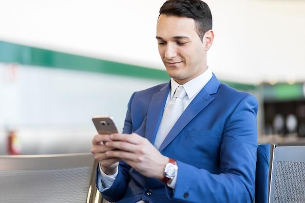 Zakenman die de telefoon met behulp van op de luchthaven