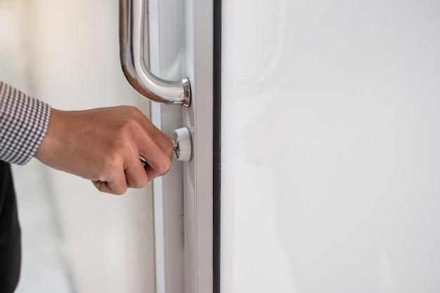 Zakenman die deurknop ontgrendelt om de deur in het kantoor te openen