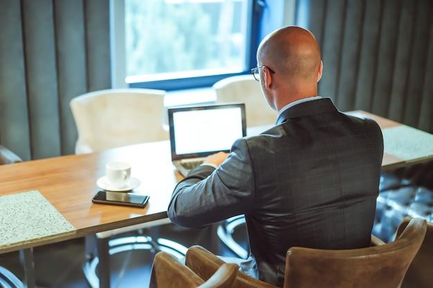 Zakenman die digitale draadloze technologie gebruikt. achteraanzicht van succesvolle blanke man aan het werk