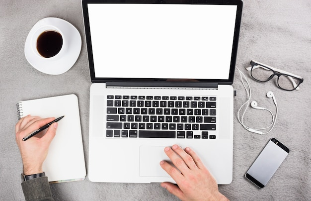 Zakenman die digitale tablet gebruiken die op klembord met pen over het grijze bureau schrijven