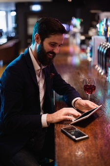 Zakenman die digitale tablet met wijnglas en mobiele telefoon op teller gebruiken