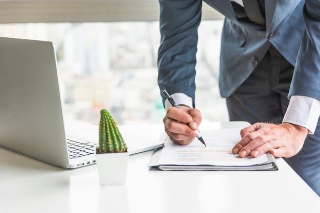 Zakenman die document met pen controleren op bureau