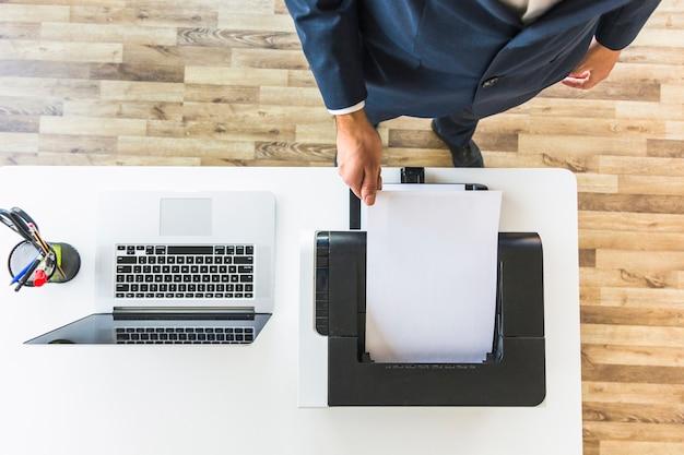Zakenman die document van printer in het bureau neemt