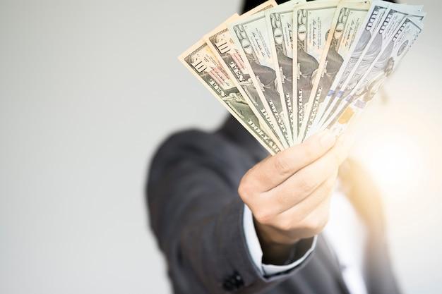 Zakenman die dollarbankbiljetten houdt
